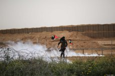 "Israeli forces shoot multiple tear gas canisters at a Palestinian woman with during the anniversary march of the ""Great March of Return"" and ""Palestinian Land Day"" protests at Israel-Gaza border located near Al Bureij Refugee Camp in Gaza City, Gaza on March 30, 2019 [Hassan Jedi / Anadolu Agency]"