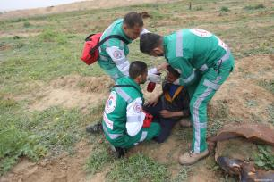 "Palestinian medical staff treat a Palestinian, affected by tear gas, during the anniversary march of the ""Great March of Return"" and ""Palestinian Land Day"" protests at Israel-Gaza border located near Al Bureij Refugee Camp in Gaza City, Gaza on March 30, 2019 [Hassan Jedi / Anadolu Agency]"