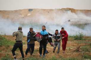 """An injured Palestinian is carried away during the anniversary march of the """"Great March of Return"""" and """"Palestinian Land Day"""" protests at Israel-Gaza border located near Al Bureij Refugee Camp in Gaza City, Gaza on March 30, 2019 [Hassan Jedi / Anadolu Agency]"""