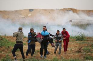"An injured Palestinian is carried away during the anniversary march of the ""Great March of Return"" and ""Palestinian Land Day"" protests at Israel-Gaza border located near Al Bureij Refugee Camp in Gaza City, Gaza on March 30, 2019 [Hassan Jedi / Anadolu Agency]"