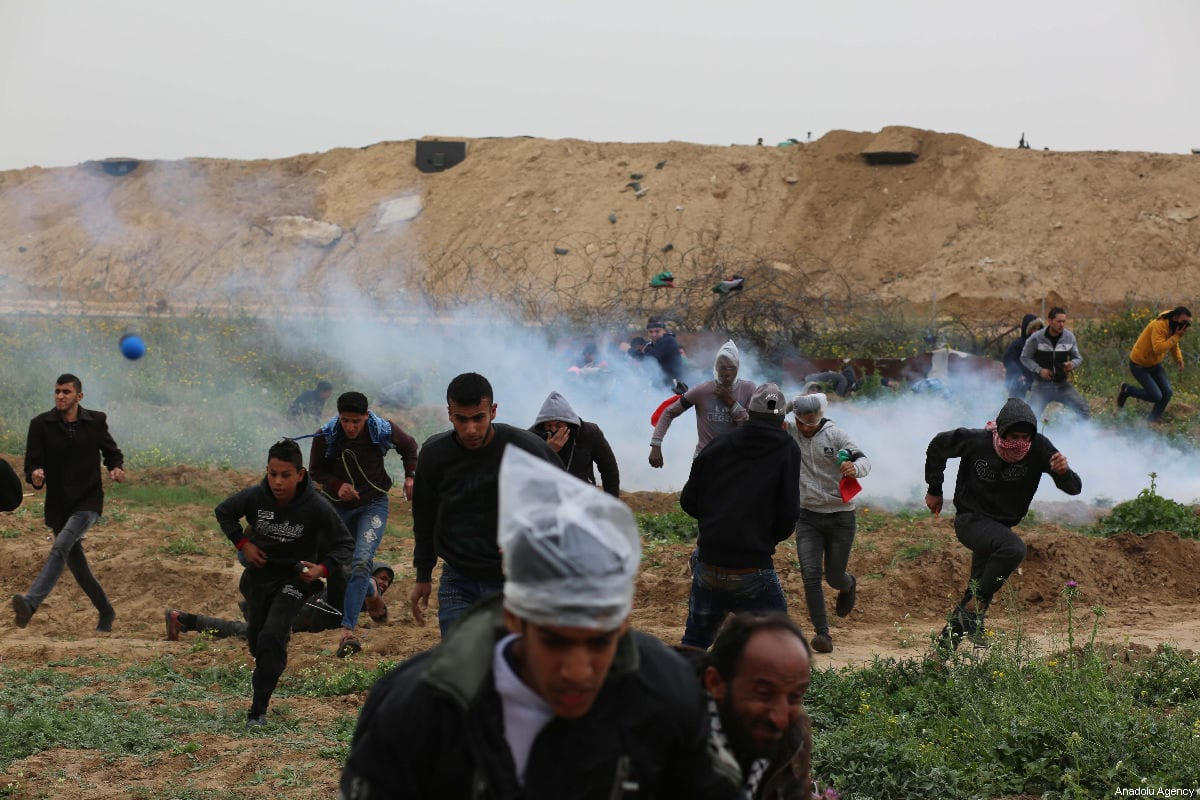 """Israeli forces intervene Palestinians with tear gas during a protest within the """"Great March of Return"""" and """"Palestinian Land Day"""" demonstrations at Israel-Gaza border located near Al Bureij Refugee Camp in Gaza City, Gaza on 03 March 2019. [Hassan Jedi - Anadolu Agency]"""