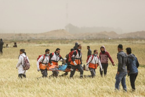 """Palestinian medical staff carry away an injured Palestinian during a protest within the """"Great March of Return"""" and """"Palestinian Land Day"""" demonstrations at Israel-Gaza border in Khan Yunis, Gaza on 30 March 2019. [Mustafa Hassona - Anadolu Agency]"""