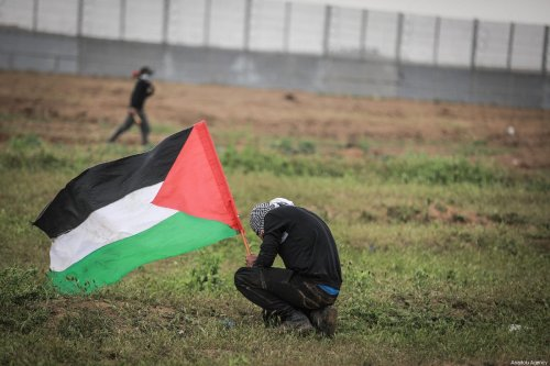 """A Palestinian holds a flag during a protest within the """"Great March of Return"""" and """"Palestinian Land Day"""" demonstrations in east of Shuja'iyya neighborhood, Gaza City, Gaza on March 30, 2019 [Ali Jadallah / Anadolu Agency]"""