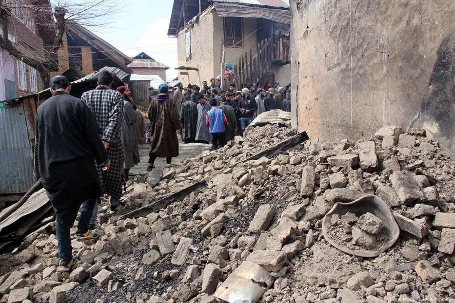 Kashmiri villagers walk past the debris of a house which was damaged by Indian forces in Kashmir on 5 March 2019 [Faisal Khan/Anadolu Agency]