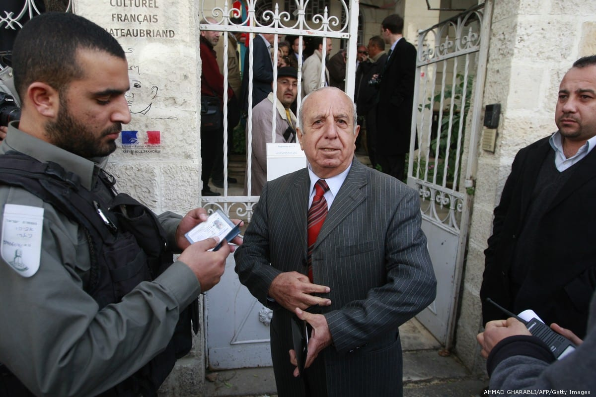 An Israeli border policeman checks the ID of a Palestinian man at the French cultural centre in Jerusalem, on 17 December 2009 [AHMAD GHARABLI/AFP/Getty Images]