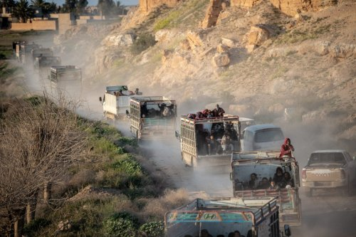 People who fled Daesh can be seen in the back of trucks in an area controlled by the Kurdish-led Syrian Democratic Foces (SDF) on 4 March 2019 [Bulent KILIC/AFP/Getty]