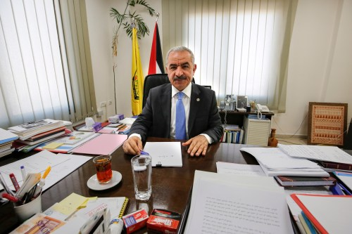 Newly-appointed Palestinian Prime Minister Mohammad Shtayyeh sits behind his desk at his office in the West Bank city of Ramallah on 10 March, 2019 [ABBAS MOMANI/AFP/Getty Images]