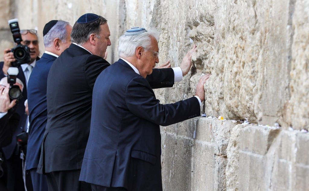 (L to R) Israeli Prime Minister Benjamin Netanyahu, US Secretary of State Mike Pompeo, and US ambassador to Israel David Friedman, touch the stones of the Western Wall in Jerusalem's Old City on March 21, 2019, during the second day of Pompeo's visit as part of his five-day regional tour of the Middle East. [ABIR SULTAN/AFP/Getty Images]
