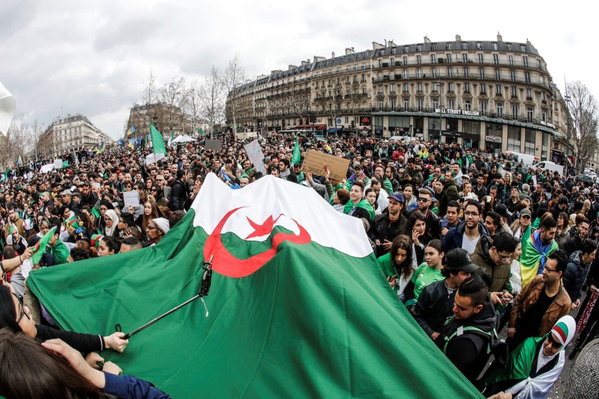 Demonstrators wave Algerian flags during a protest over fears of plot to prolong the Algerian president's rule, on Place de la Republique (Republic's Square) in Paris, on 24 March, 2019 [FRANCOIS GUILLOT/AFP/Getty]