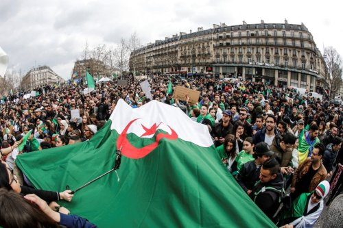 Demonstrators wave Algerian flags during a protest over fears of plot to prolong the Algerian president's rule, on Place de la Republique (Republic's Square) in Paris, on 24 March, 2019 [FRANCOIS GUILLOT/AFP/Getty]