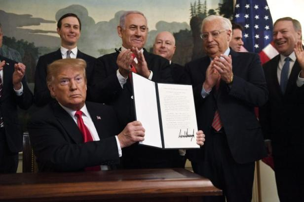President Donald Trump holds up an executive proclamation recognizing the Golan Heights as Israeli territory at the White House in Washington DC, Monday, 25 March, 2019 [Getty]