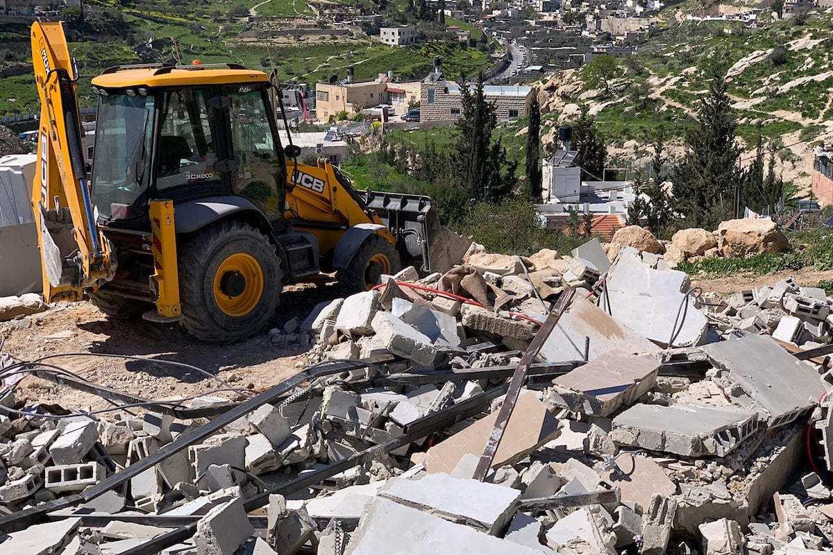 A bulldozer demolishes two Palestinian house in Jabal al-Mukaber, in Jerusalem, on 9 March 2019. [Afif Amera/WAFA/APAimages]