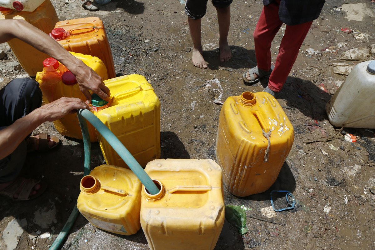 Yemeni people fill plastic barrels with clean water, distributed by charities, in Madhbah village of Sana'a, Yemen on 1 April, 2019 [Mohammed Hamoud/Anadolu Agency]