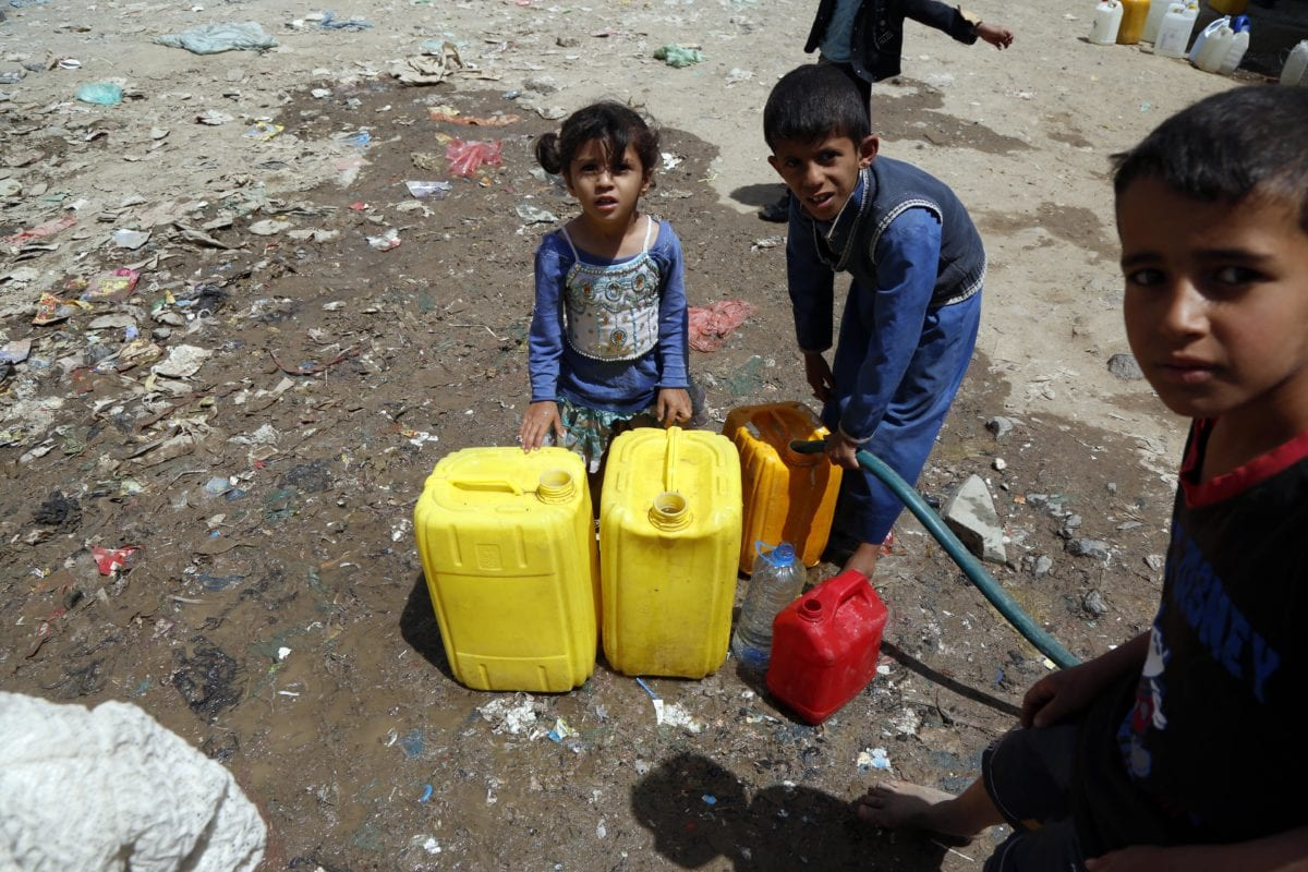 Yemeni people fill plastic barrels with clean water, distributed by charities, in Madhbah village of Sana'a, Yemen on April 1, 2019. [Mohammed Hamoud - Anadolu Agency]