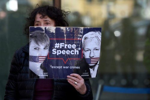 "A protester holds a banner reading ""Free Speech - Except War Crimes"" during a protest outside Westminster Magistrates court, in London, United Kingdom on 11 April 2019. [Kate Green - Anadolu Agency]"