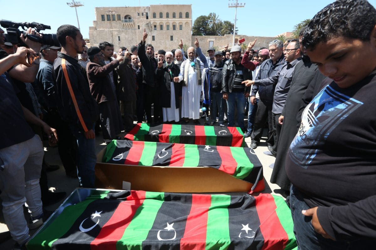 People shout slogans near flag-draped coffins of those who lost their lives in rocket attacks by East Libya-based forces led by commander Khalifa Haftar at the Abu Salim neighborhood, during a funeral ceremony at Martyrs' Square in Tripoli, Libya on 17 April 2019. [Hazem Turkia - Anadolu Agency]