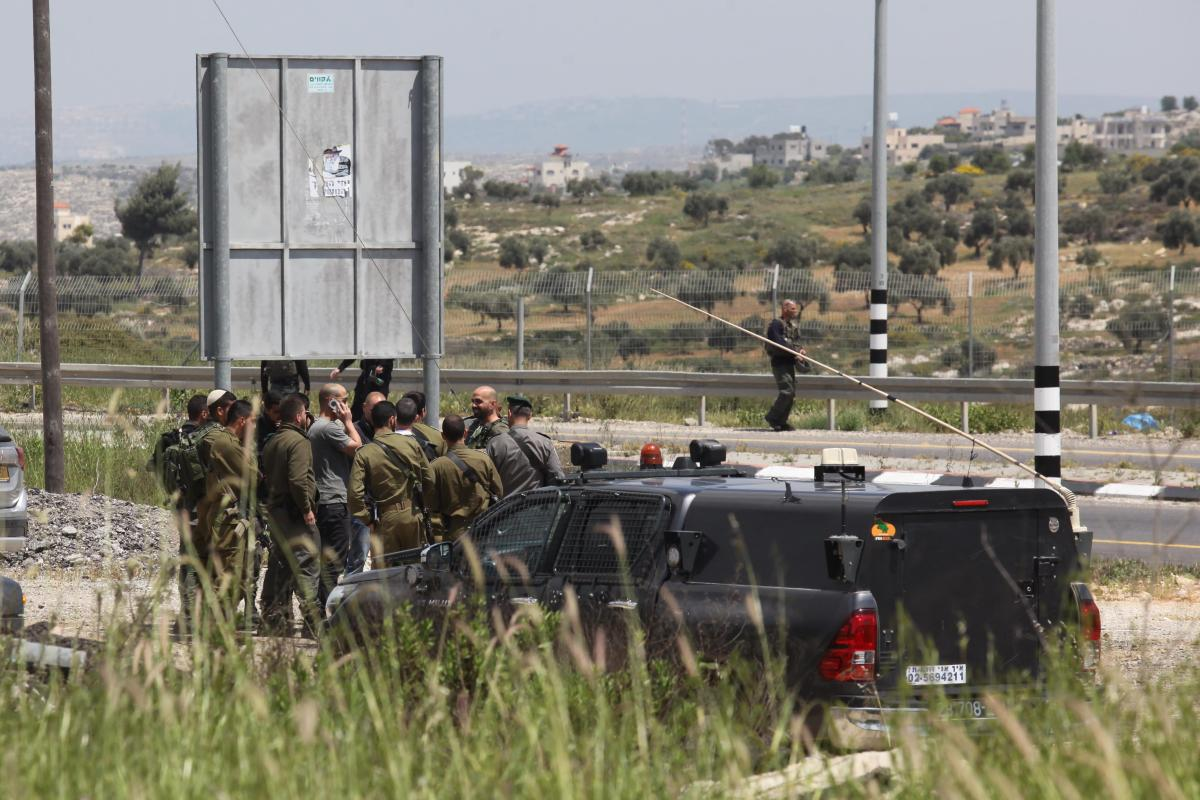 Israeli soldiers inspect the site where an alleged Palestinian knife attacker was shot and killed by Israeli security forces, near Nablus in the northern West Bank, on 20 April, 2019 [Nedal Eshtayah/Anadolu Agency]