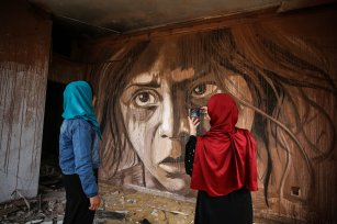 """Palestinian artist Ali al-Jabali displays his paintings composed of portraits of children, women, elders and young people at his exhibition named """"Dreamers among the rubbles"""" on the walls of buildings, which have been damaged on Israeli attacks on July 2014, at al-Nasr neighborhood in Gaza City, Gaza on 24 April 2019 Ali al-Jabali has painted four walls and six oil paintings to draw attention to the difficulties of Palestinians in Gaza [Mustafa Hassona/Anadolu Agency]"""