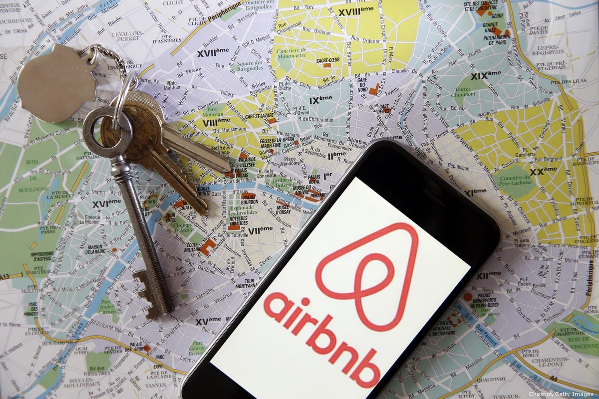 Photo illustration of Airbnb is displayed on the screen of an iPhone placed on a map [Chesnot/Getty Images]