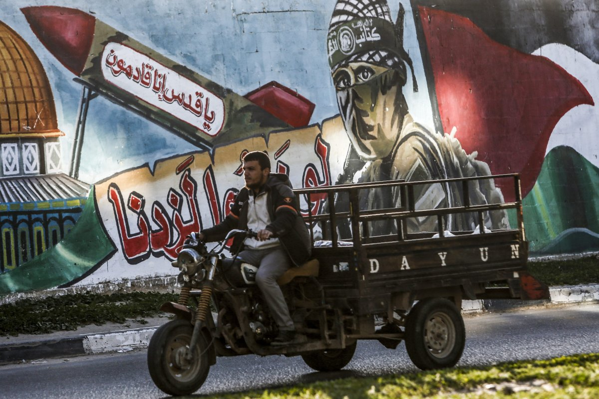 """A Palestinian man drives a motorcycle cart past a mural depicting a masked fighter of the Qassam Brigades, the armed wing of the Hamas movement, next to a missile with a caption reading in Arabic """"Oh Jerusalem, we are coming"""" and the Dome of the Rock, in a street in Rafah in the southern Gaza Strip on 14 March, 2019 [SAID KHATIB/AFP/Getty]"""