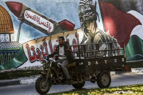 "A Palestinian man drives a motorcycle cart past a mural depicting a masked fighter of the Qassam Brigades, the armed wing of the Hamas movement, next to a missile with a caption reading in Arabic ""Oh Jerusalem, we are coming"" and the Dome of the Rock, in a street in Rafah in the southern Gaza Strip on 14 March, 2019 [SAID KHATIB/AFP/Getty]"