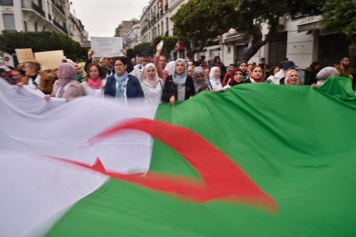 Algerians carry a giant national flag as they take part in a demonstration in the capital Algiers against President Abdelaziz Bouteflika on 19 March, 2019 [RYAD KRAMDI/AFP/Getty]