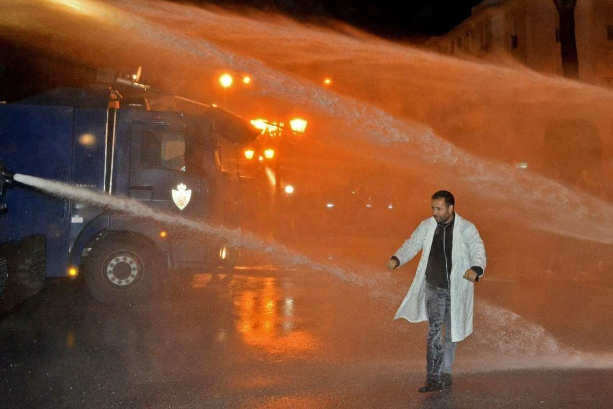 A Moroccan teacher walks through a water spray from security forces' water cannon during a demonstration calling for permanent contracts within the national education system, outside parliament headquarters in the capital Rabat on 25 April 2019. [ AFP/ Getty]
