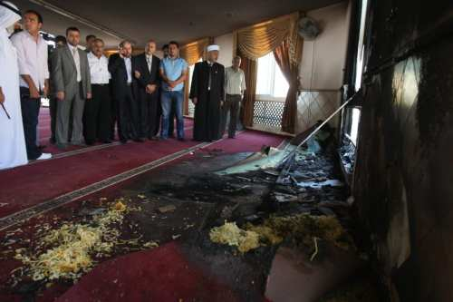 Palestinians from the village of Jabaa, east of Ramallah, look at damage at a mosque which settlers tried to burn overnight on June 19, 2012. [AFP PHOTO/ABBAS MOMANI / Getty]