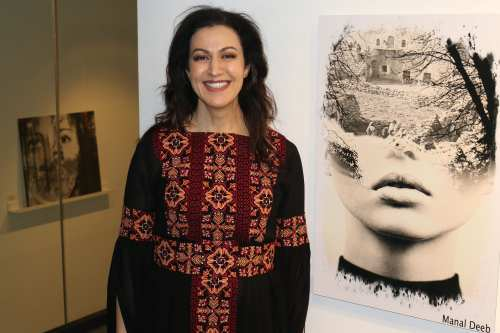 Palestinian-American artist Manal Deeb poses in front of her art piece 'Sinseleh' at P21 Gallery on 5 April 2019 {Jehan Alfarra/Middle East Monitor]