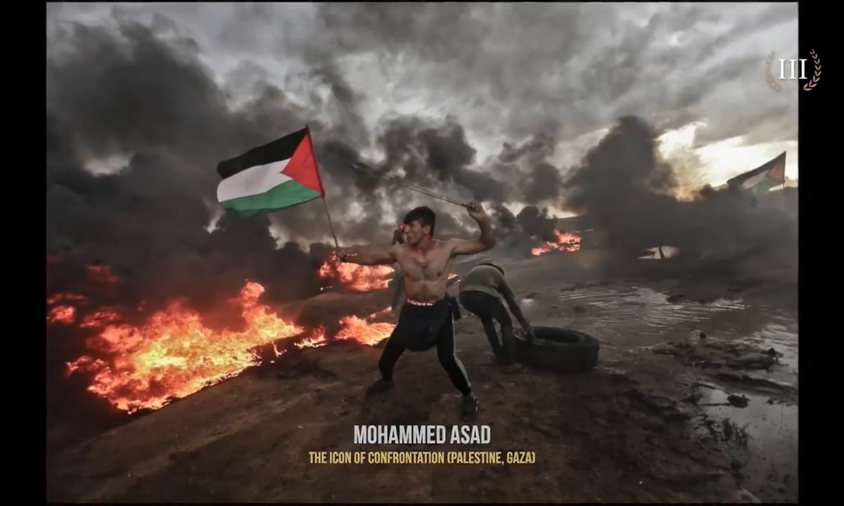 Palestinian man carrying a slingshot and the Palestinian flag while taking part in the Great March of Return protests at the Gaza-Israel fence, wins Best Photograph in Street category during the 4th annual International Photography 35Awards [Mohammed Asad]