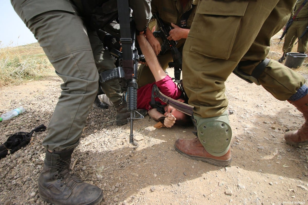 A volunteer helping fill potholes on the central road near South Hebron on 3 May 2019 is handcuffed by Israeli occupation forces and then dragged through the street to a military vehicle were he was then taken to an Israel police station and charged with refusing to obey a military order. [Ahmad Al-Bazz]
