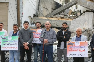 Anadolu Agency's Gaza representative Yasser al-Benna (C) speaks during a demonstration as journalists gather in front of the wreckage of the Anadolu Agency's office after it was hit by Israeli warplanes' in 5 Gaza, 2019 [Mustafa Hassona/Anadolu Agency]