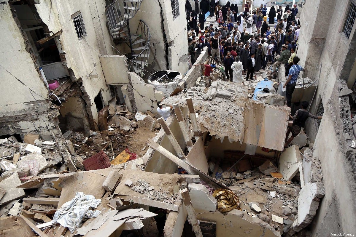 People gather round damaged buildings after the Saudi-led military coalition carried our air strikes in Sanaa, Yemen on 16 May 2019 [Mohammed Hamoud/Anadolu Agency]