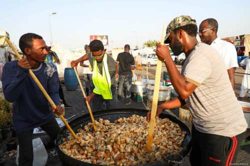 Sudanese volunteer demonstrators prepare food for the iftar (fast-breaking) dinner on the Holy month of Ramadan, around the demonstration area during ongoing protests demanding a civilian transition government in front of military headquarters, in Khartoum, Sudan on 6 May, 2019 [Mahmoud Hjaj/Anadolu Agency]