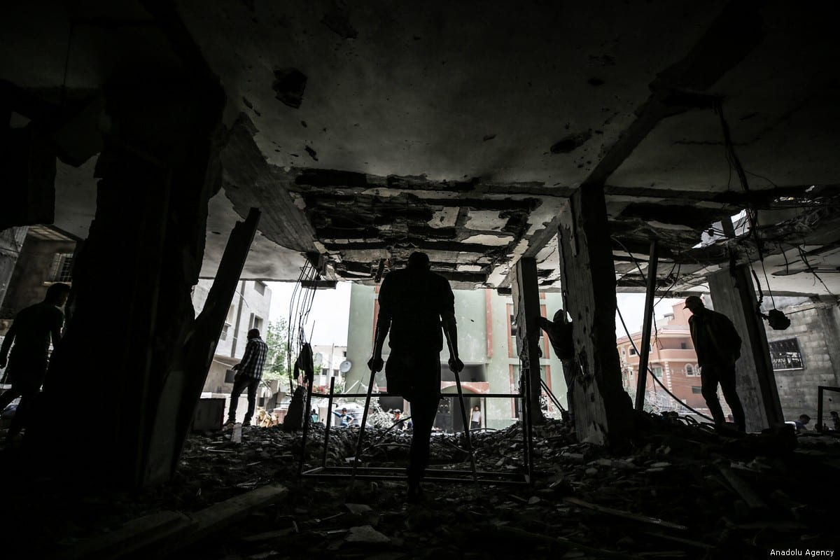 Silhouettes of centre staff and people with disabilities inspecting the damaged building of Confederation of Disabled People, which was the only centre to serve people with disabilities in Rafah, after Israel's attacks on Gaza in Rafah, Gaza on 7 May, 2019 [Ali Jadallah/Anadolu Agency]