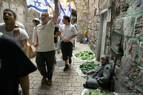 Israeli youths match through the Old City of Jerusalem holding the Israeli flag marking 'Jerusalem Day' on 16 May 2007 [MENAHEM KAHANA/AFP/Getty Images]