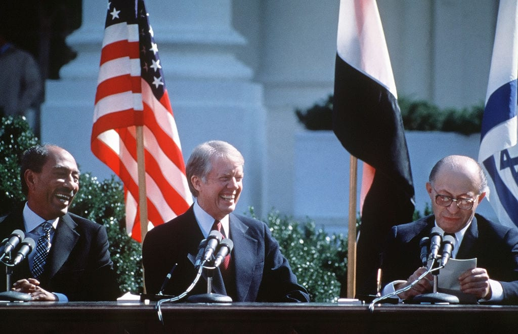 Egyptian President Anwar al-Sadat (L) and US President Jimmy Carter laugh during Israeli Premier Menachem Begin' speech (R), before signing the Israel-Egypt Peace Agreement on 26 March, 1979 on the north lawn of the White House, Washington DC [AFP/Getty Images]