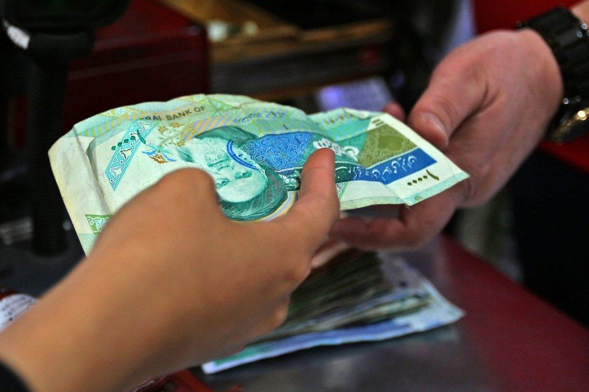 An Iranian customer pays with local currency for her purchase at a shop in Tehran, Iran on 24 April 2019 [ATTA KENARE/AFP/Getty]