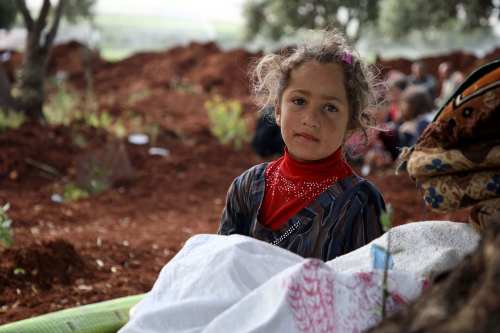 A displaced Syrian child sits in a field near a camp for displaced people in the village of Atme, in the jihadist-held northern Idlib province on May 8, 2019. - In the olive grove in Atme, dozens of families have spent the night on thin mattresses or blankets layed out over rugs on the red earth. At the base of the trees they have chosen for shelter, they have stored the bare minimum for a life outdoors: bedding, a water cooler, a saucepan, or a cooking gas canister. They have hung up sheets between the trees for a little privacy, and one family has even brought a solar panel. (Photo by Aaref WATAD / AFP) (Photo credit should read AAREF WATAD/AFP/Getty Images)