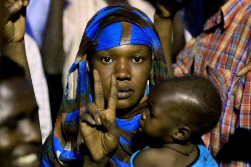 "A Sudanese woman holding a baby flashes the ""V"" for victory sign as protesters gather outside the military headquarters in the capital Khartoum demanding the instalment of civilian rule, on 27 May 2019. [ASHRAF SHAZLY / AFP/ Getty]"
