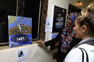 Artists and visitors look at paintings during an exhibition showcasing the work of young migrant artists at the Donia Dabanga gallery on 18 December, 2016 in the Sudanese capital Khartoum [EBRAHIM HAMID/AFP/Getty Images]