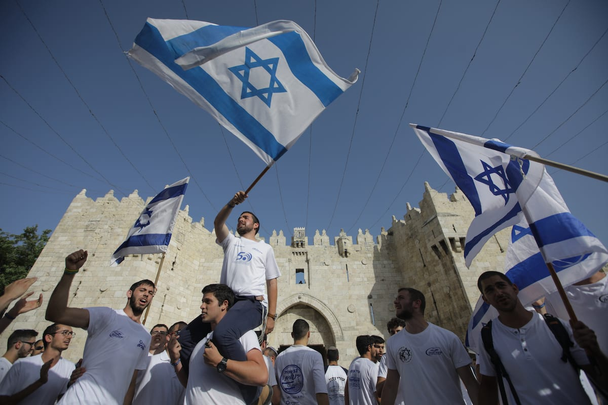 Israeli Jews wave the Israeli flag outside Damascus Gate in Jerusalem's Old City on 2 June 2019 [Faiz Abu Rmeleh/Anadolu Agency]
