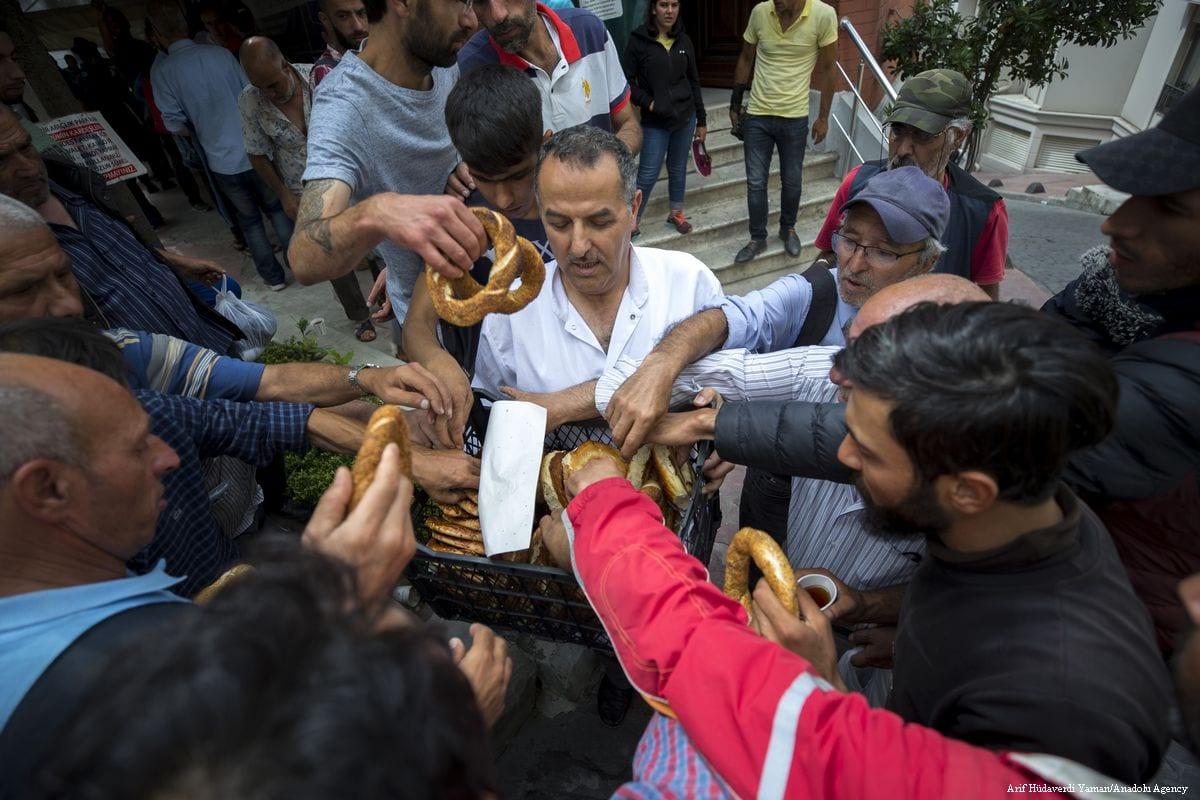 Imam Osman Gokrem (C) offers bagels to homeless people at the Selime Hatun Mosque in Istanbul, Turkey on 29 June 2019 [Arif Hüdaverdi Yaman/Anadolu Agency]