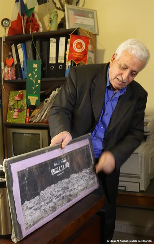 Mahmoud showing a poster of Shatila camp in 1988 [Ferdous Al-Audhali/Middle East Monitor]