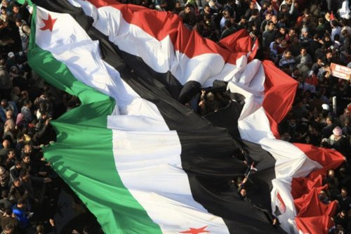 The Syrian revolutionary flag flew side by side in Tahrir Square with the Egyptian flag, during Egypt's revolutionary period [Twitter]