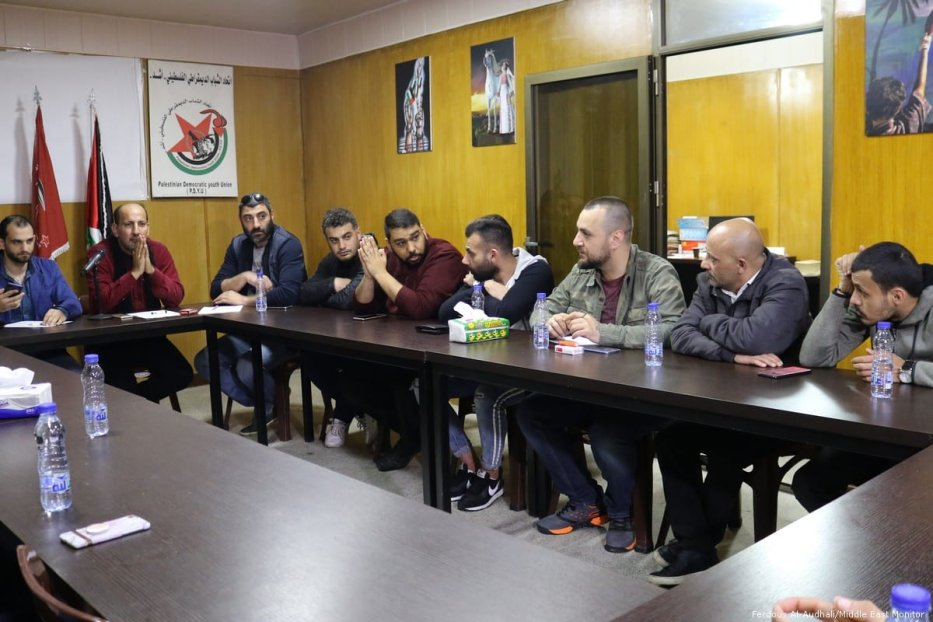Members of the youth committee in Mar Elias sit around their meeting table.