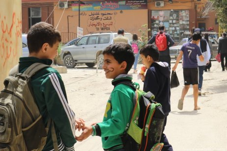 Children laugh and talk as they walk home from school.
