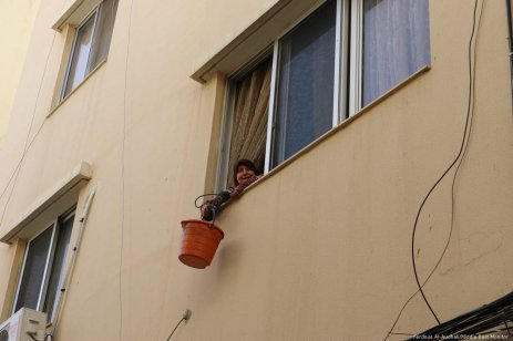 A resident of Nahr Al-Bared smiles at the camera as she pulls a bucket of groceries up to her window.