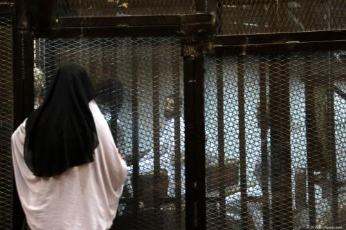 Relatives speak with Egyptian prisoners as they stand behind bars in a court in Cairo on 9 August 2015 [Stringer/Apaimages]