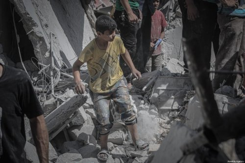 A boy, covered in dust, stands over debris after airstrikes of Assad Regime's warplanes hit the de-escalation zone of Ariha in Idlib, Syria on 12 . July 2019. [Muhammed Said - Anadolu Agency]